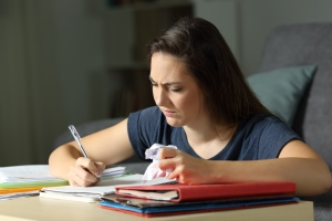 Young woman looking angry and frustrated while taking notes