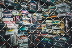 Colourful books seen through a wire fence