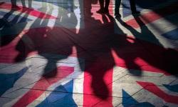 Shadows of British citizens on Union Jack flag