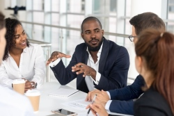 Man confidently sharing thoughts at a business meeting