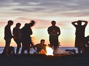 A group of people enjoying a beach campfire at sunset