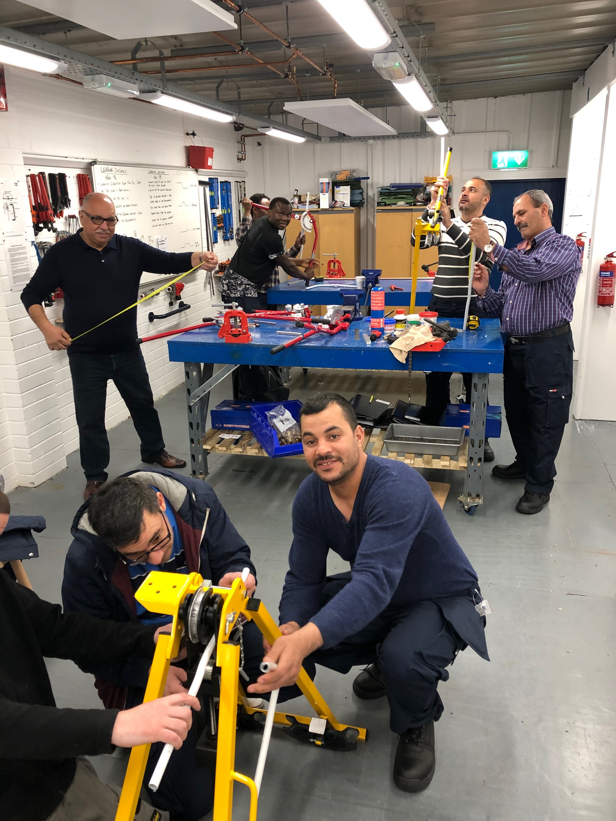 A photo of refugee men using tools in a workshop. They are taking part in a Belfast based innovative language and employability programme for refugees developed by Conway Education Centre.