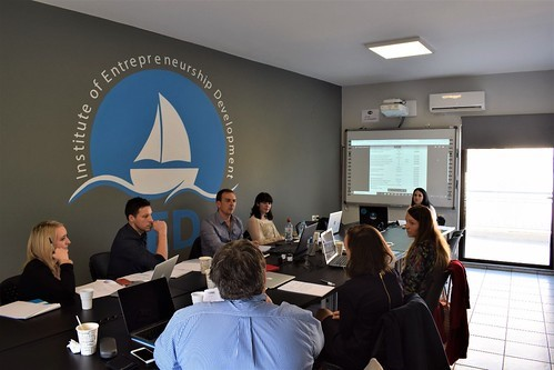 "A group of young adults with laptops sit around a conference table. The design on the wall is a sailboat and the words ""Institute of Entrepreneurship Development""."