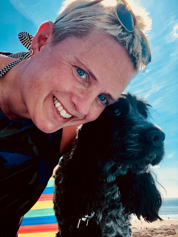 A photo of Elaine Williams with her dog at the beach.