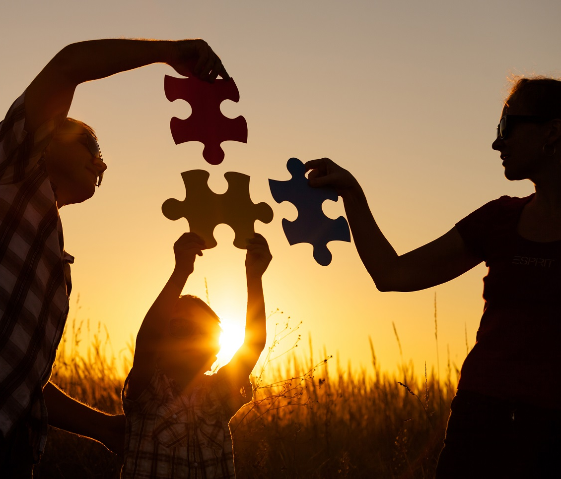 A mother, father, and child each hold a piece of a puzzle in front of the setting sun while standing in a wheat field