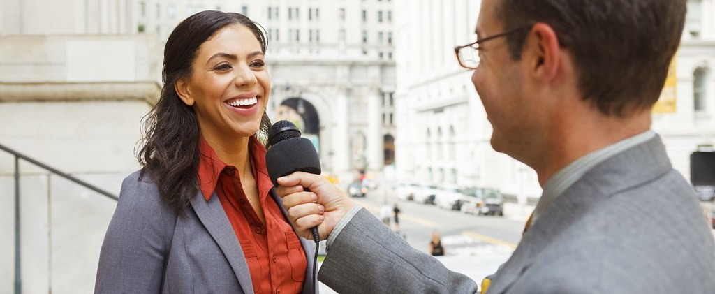 A man wearing a suit is holding up a microphone in front of a woman who is smiling and also wearing a suit. They are standing on the front steps of a building.
