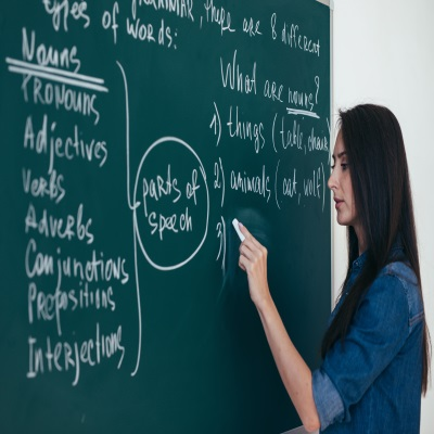 English for Speakers of Other Languages teacher writing on blackboard