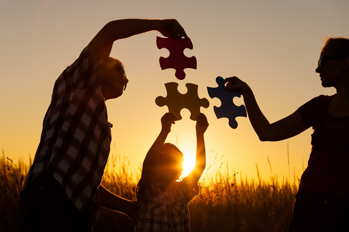 The silhouettes of 2 parents and a child each holding a giant puzzle piece against the backdrop of a sunset.