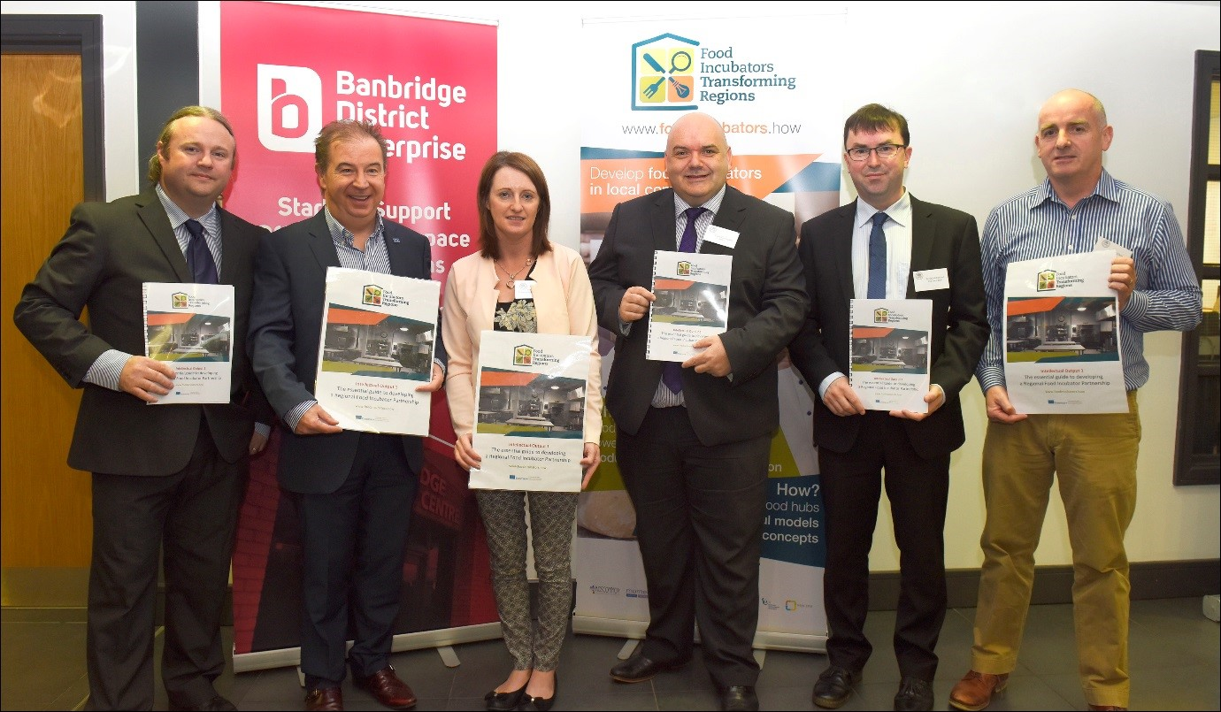 "6 people holding ""Food incubators transforming regions"" project documents in front of a Banbridge District Enterprise banner."
