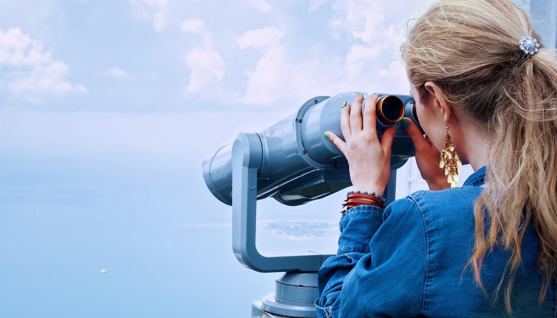 Das Bild zeigt eine junge Frau, die durch ein Fernglas sieht.