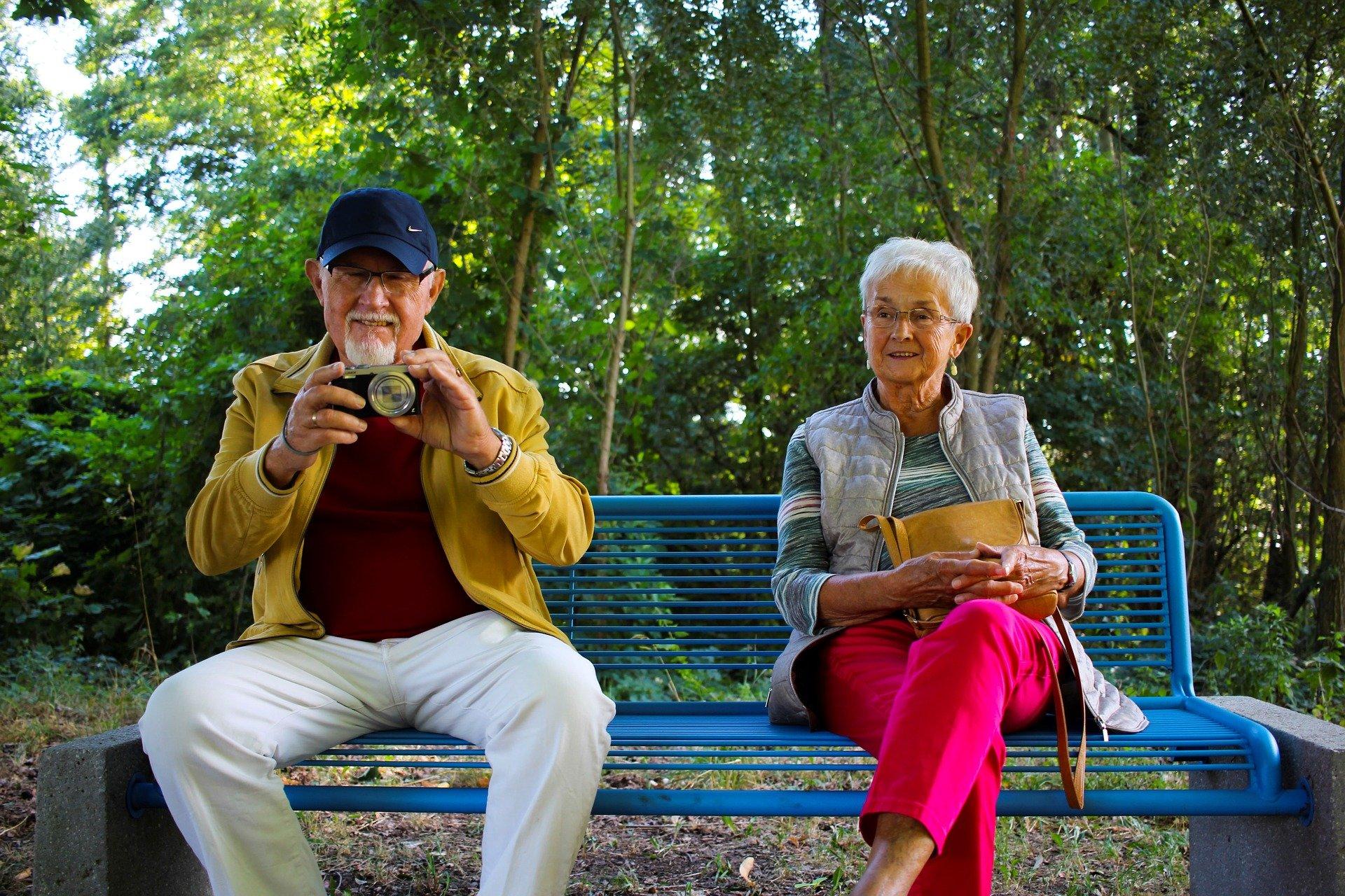 Ein Seniorenpaar sitzt auf einer Parkbank.
