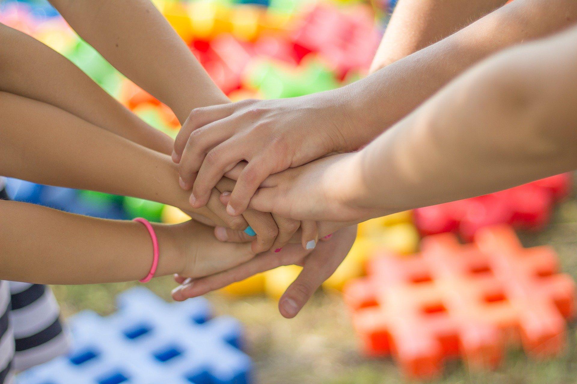 Das Bild zeigt Hände von vielen Personen, die aufeinanderliegen und zusammenhalten.