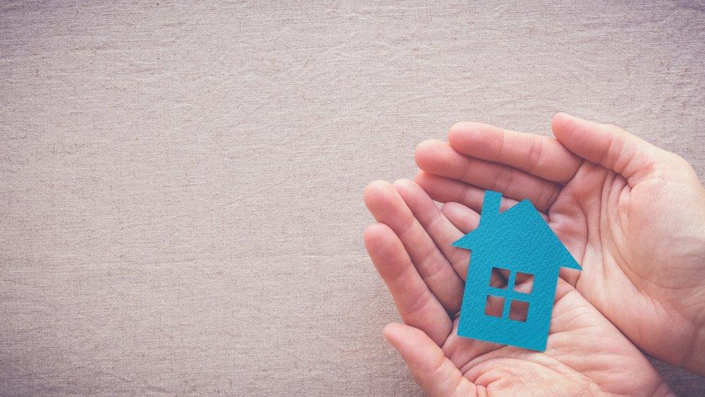 A pair of hands holds a blue paper house