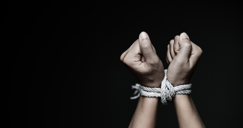Hands tied with rope against a black background