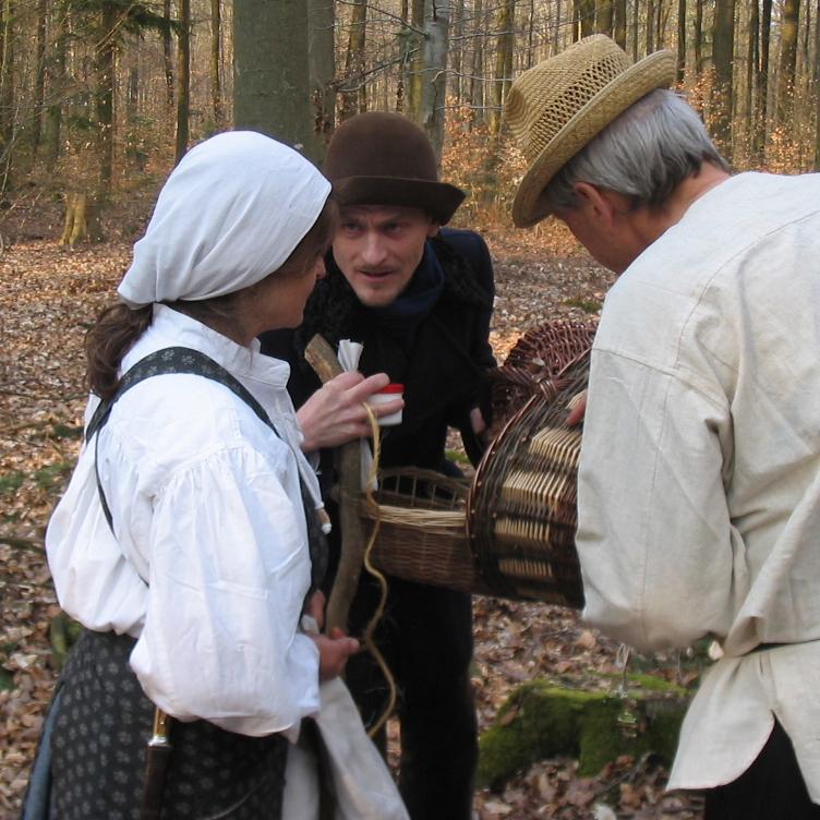Personen in historischen Kostümen stellen eine Situation nach