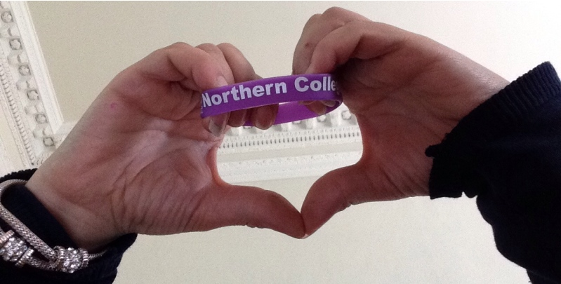 A student's hands holding up the Northern College wristband with her thumbs forming a heart below