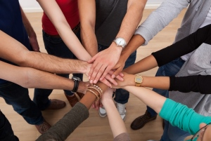 Group stacking hands to demonstrate inclusion