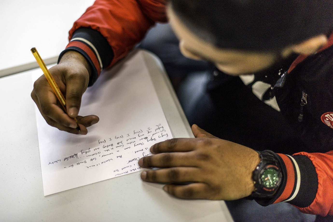 A photo of an incarcerated learner writing song lyrics