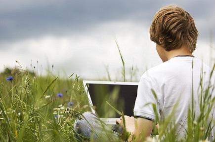 Junger Mann mit Tablet auf einer Wiese