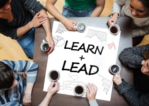 Learn and lead written on paper surrounded by colleagues at a table drinking coffee