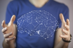 Man with hands held out beside image of a virtual brain
