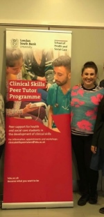 Melissa Smith standing beside a Peer Tutor Programme poster