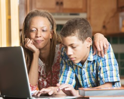 Mother and teenage son on laptop