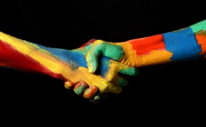 Multicoloured painted arms reaching out to each other and hands shaking