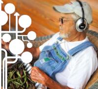 Älterer Bauer mit Kopfhörern schaut auf Tablet