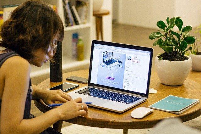 Eine Frau sitz an einem Tisch und lernt am Computer.