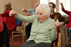 Elderly citizens taking part in an exercise class in a community centre