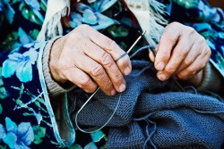 Old woman knitting clothing