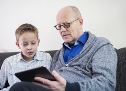 Older man reading with young boy