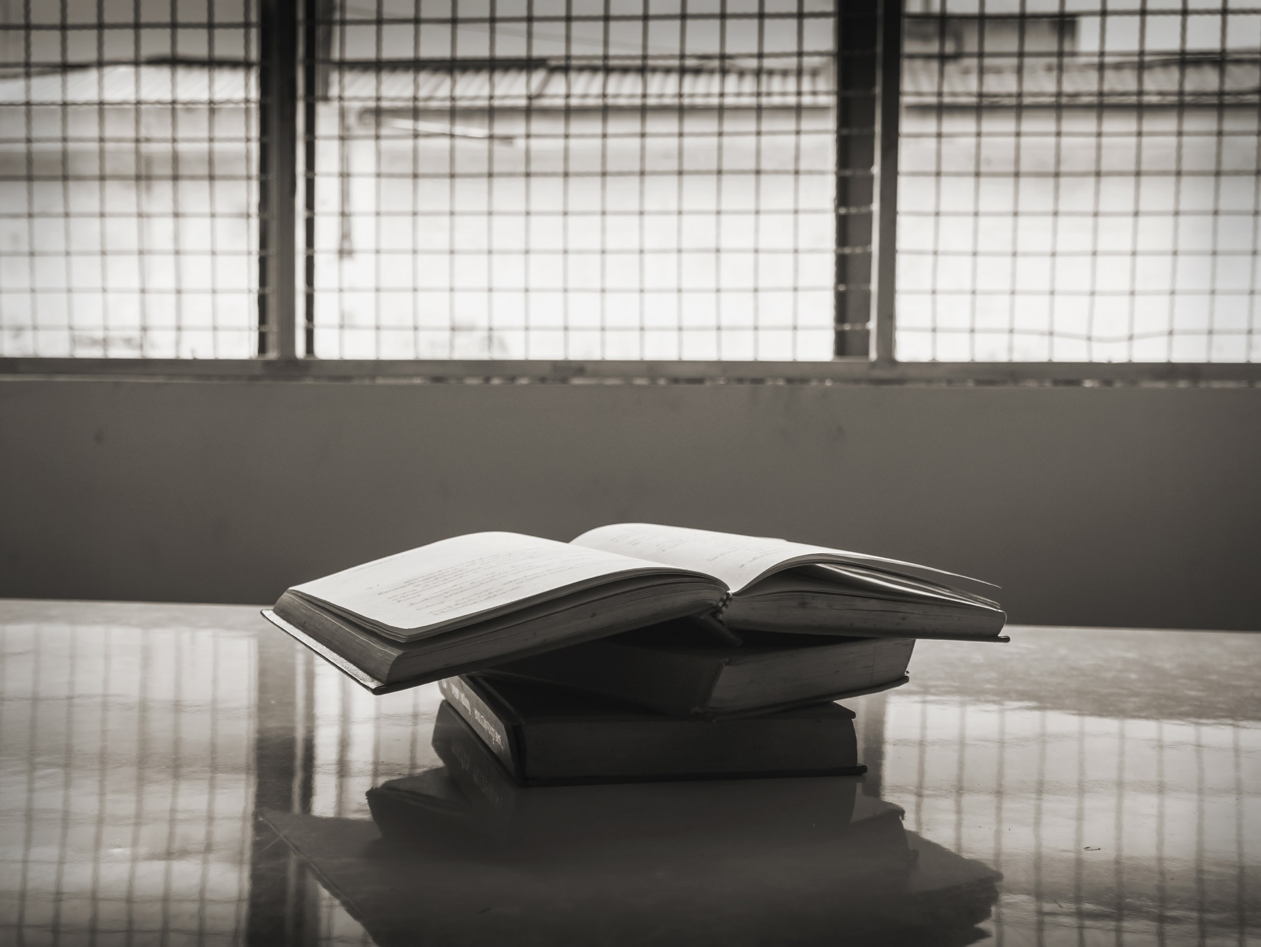 A photo of a pile of books on a table in a prison.