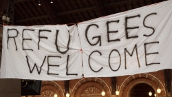 Sign reading 'refugees welcome' outside a building at night
