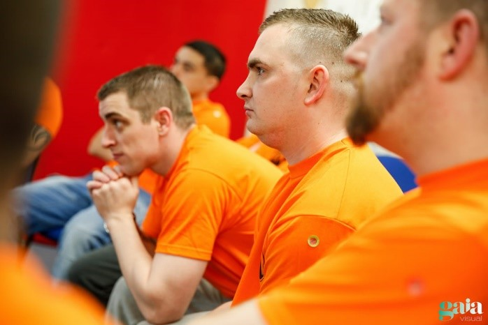 A group of men in orange t-shirts are seated in a row and paying attention to what is happening at the front of the room