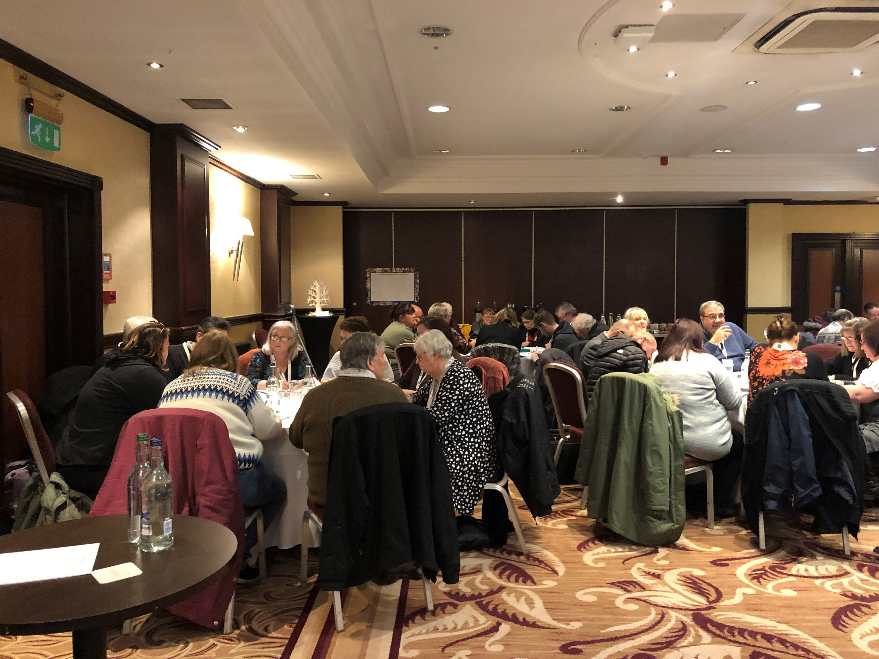 A photo of attendees of Scotland's Learners' Forum & Impact Forum meeting 2020 sitting around conference tables.