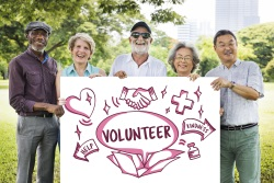Senior volunteers holding a sign that encourages volunteering