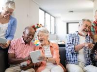 A collection of elderly people sitting on a couch together and looking at electronic tablets while smiling.