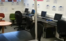 A photo of a workplace with tables and desktop computers, there is a pole holding the ceiling up in the middle