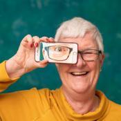 Ältere Frau mit Smartphone, in dem ihr Auge abgebildet ist, lachend