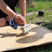 Eine Person die Pappe mit Pinsel bestreicht