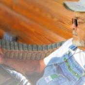 Ein alter Mann sitzt mit Köpfhörern und einem Tablet im Stuhl und putzt Bohnen.