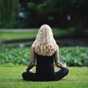 Woman meditating on a lawn