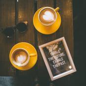 Kuva kahvikupeista pöydällä. Pöydän päällä olevassa taulussa lukee; Inhale the future, Exhale the past