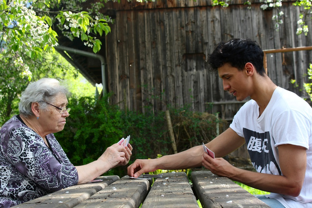 A photo from the Track project (copyright Hannah Müller) of a young man playing cards with an elderly woman at a picnic table outside.