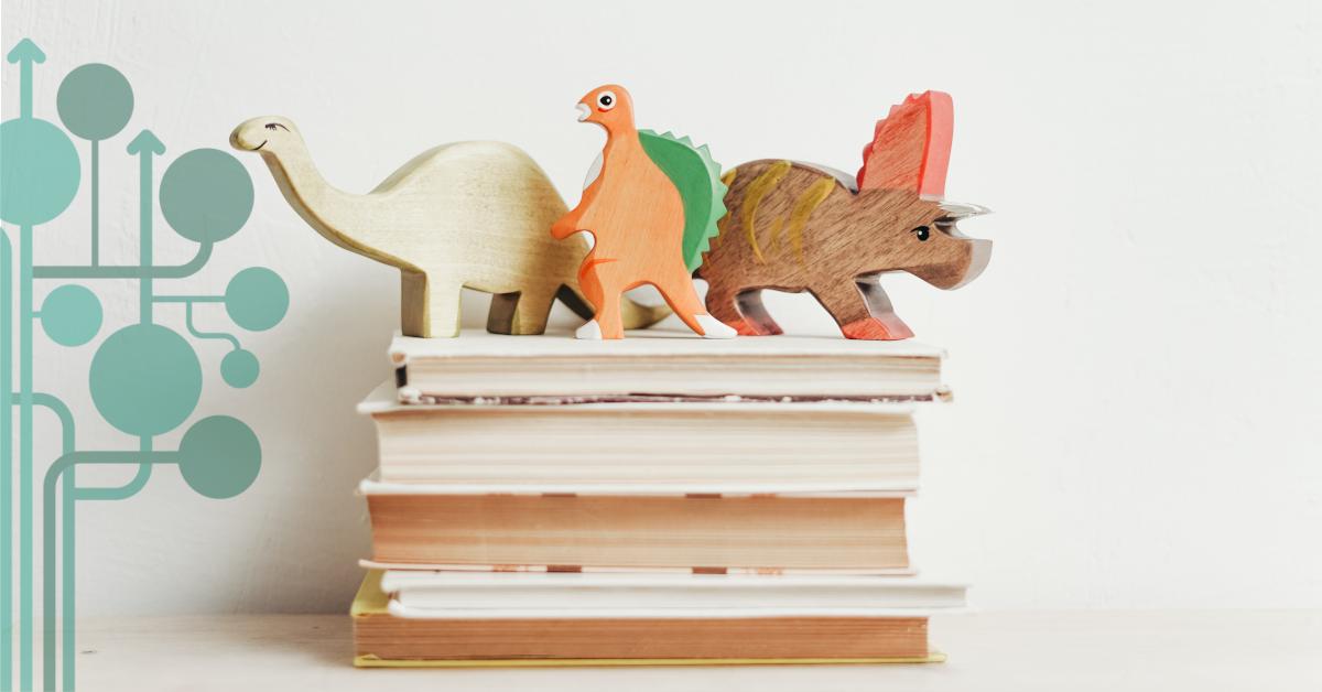 drewniane figurki dinozaurów stojące na książkach