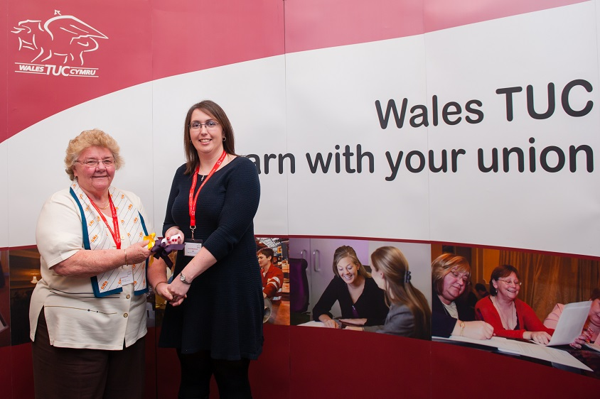 "Laura Westwood and her colleague stand in front of a large banner that reads ""Wales TUC: Learn with your union"""