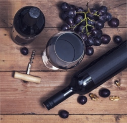 Wine bottle on table with glass, bottle opener and bunch of grapes