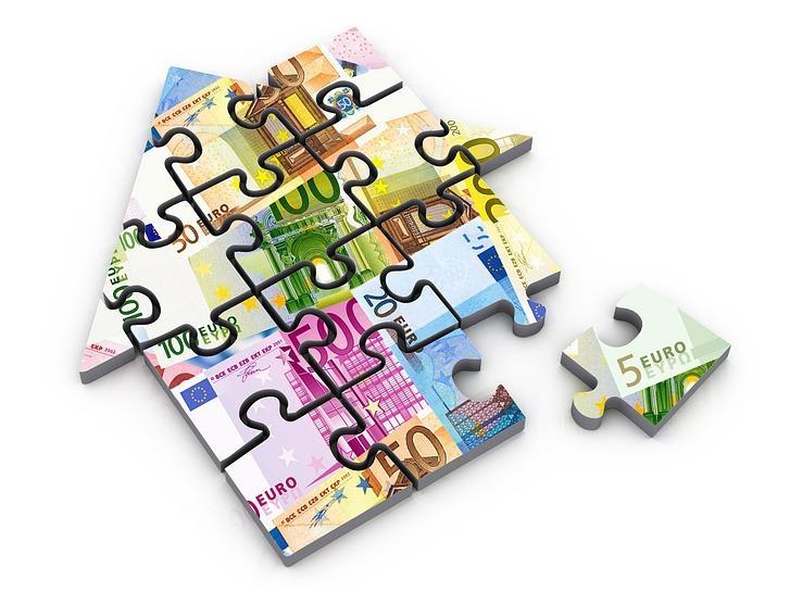 Die Grafik zeigt ein Haus, das aus mit Geldscheinen bedruckten Puzzlesteinen besteht.